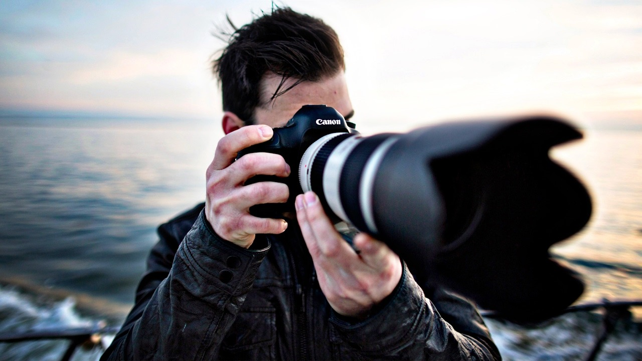 photographer using a canon DSLR to take pictures
